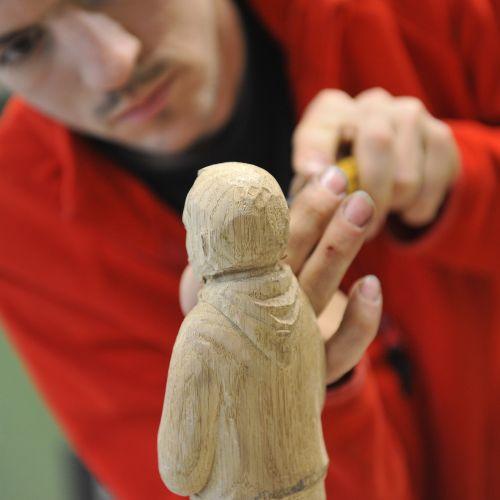 L'ébéniste sculpte un personnage